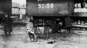 Children gathering coal behind boxcars. Place unknown. Credit: Library and Archives Canada / C-085579